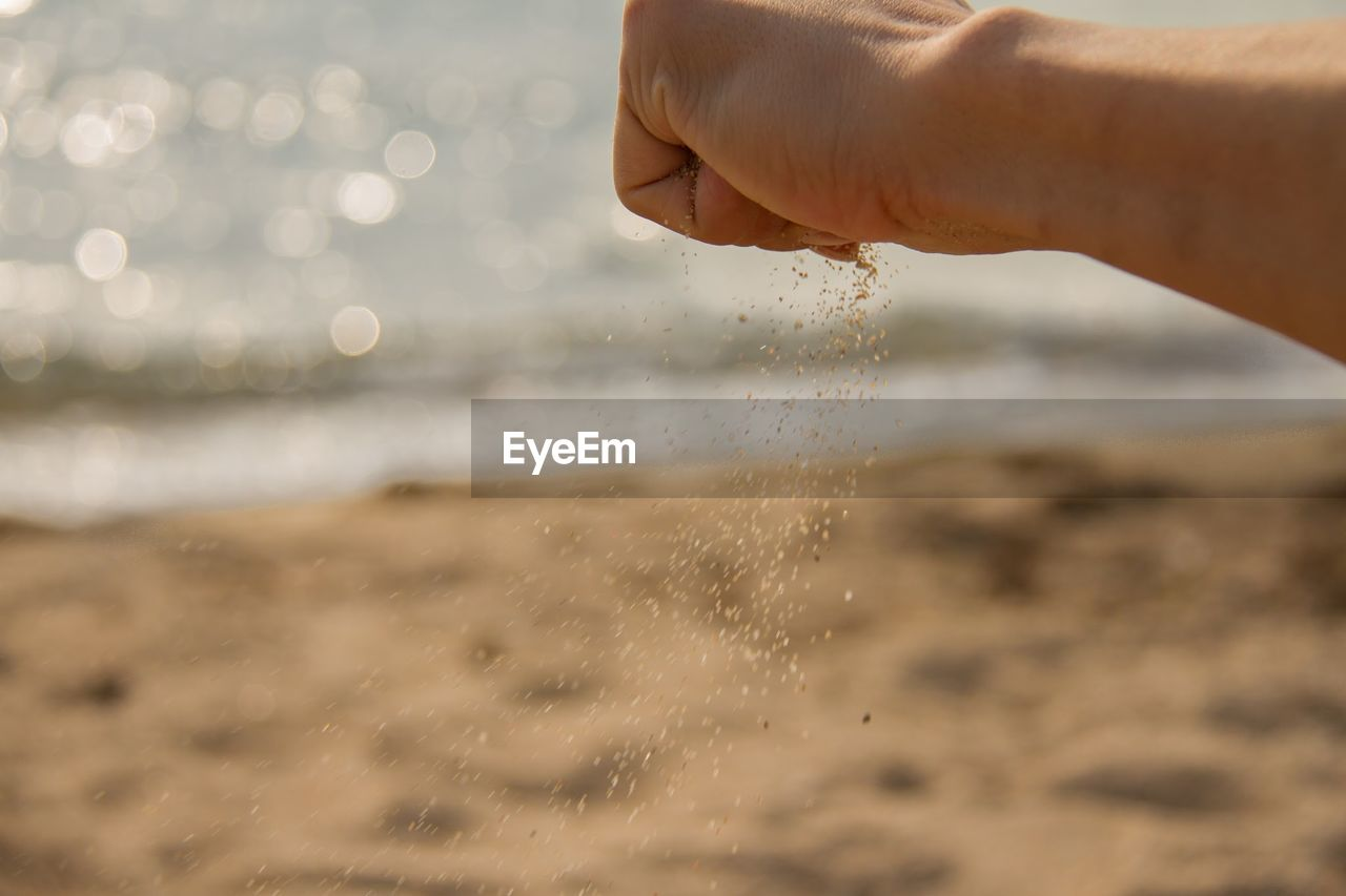 human hand, human body part, water, real people, beach, one person, sea, nature, sand, focus on foreground, beauty in nature, outdoors, lifestyles, close-up, day, horizon over water, sky