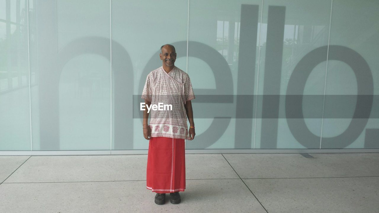Full length of man wearing traditional clothing standing against wall