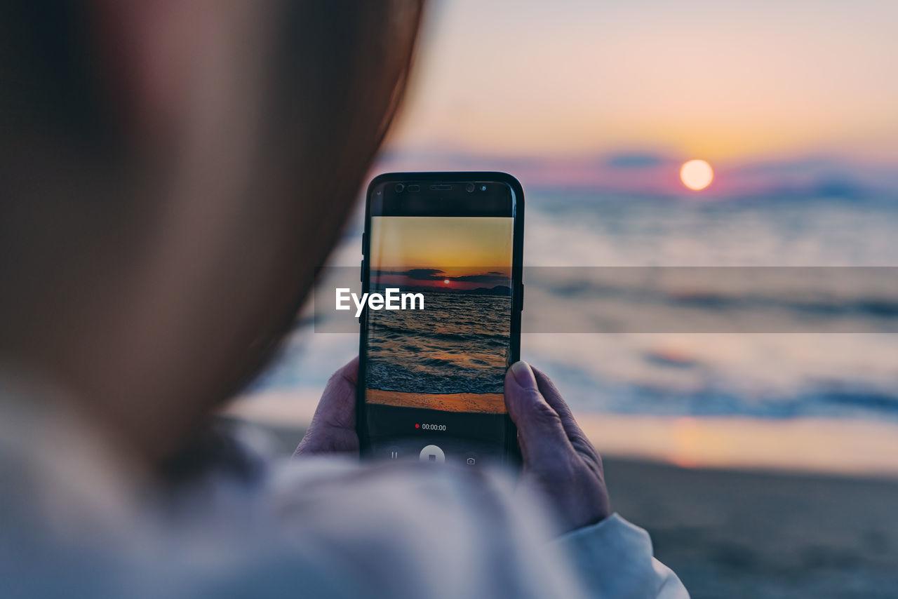 Man Photographing Sea Through Smart Phone During Sunset
