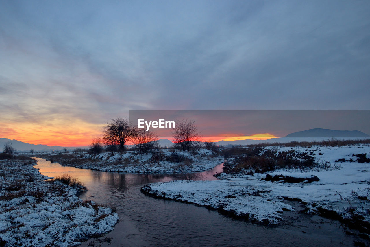sky, winter, cold temperature, sunset, snow, scenics - nature, cloud - sky, beauty in nature, tranquility, tranquil scene, nature, orange color, no people, tree, plant, environment, covering, non-urban scene, water, outdoors, snowcapped mountain