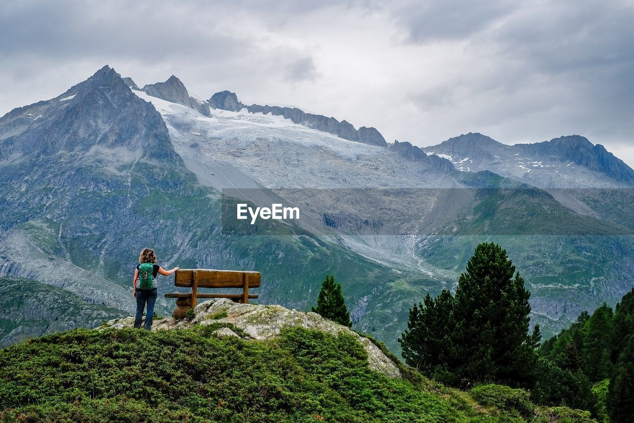 Rear View Of Female Hiker Standing By Bench On Mountain Peak Against Sky