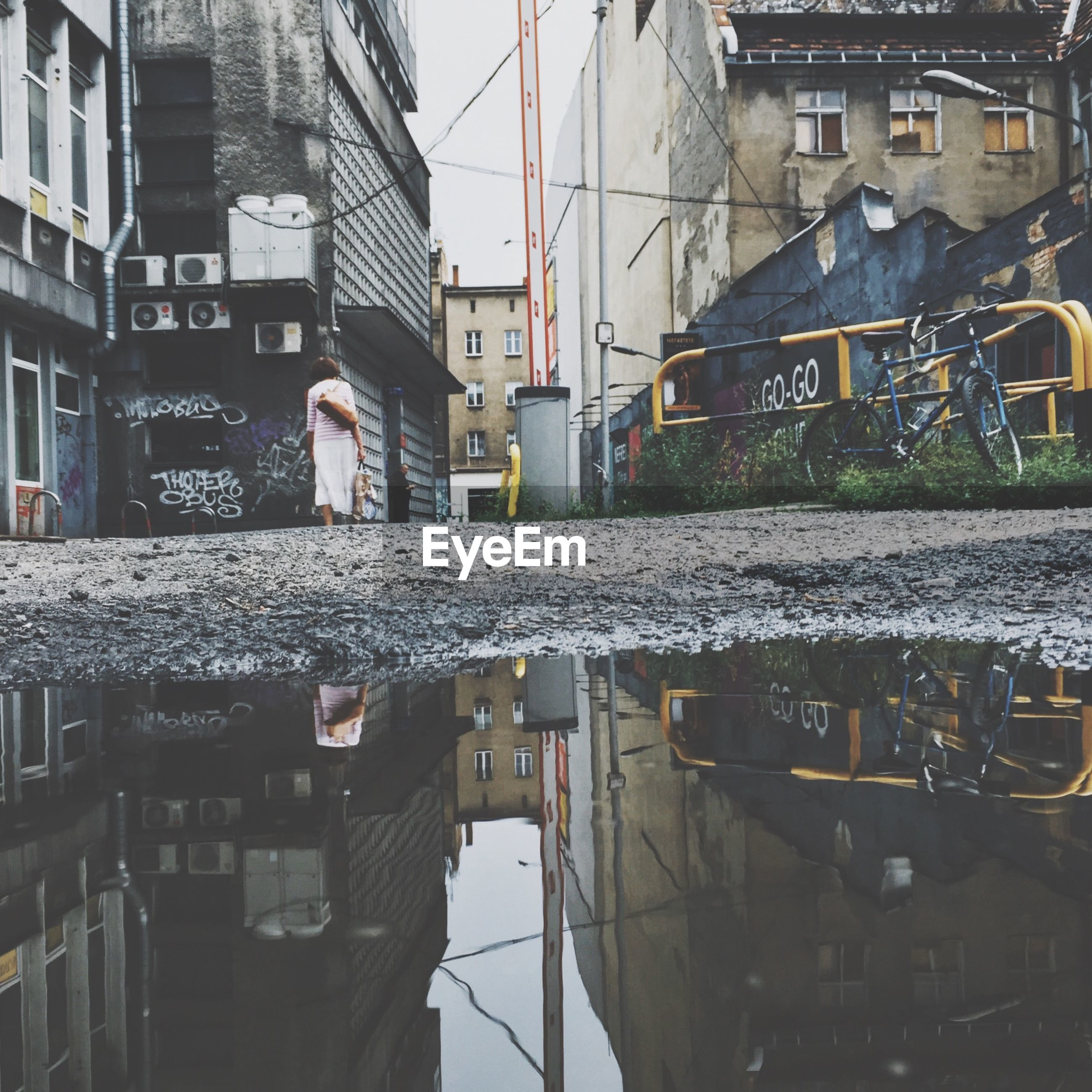 Puddle on street with woman seen in background