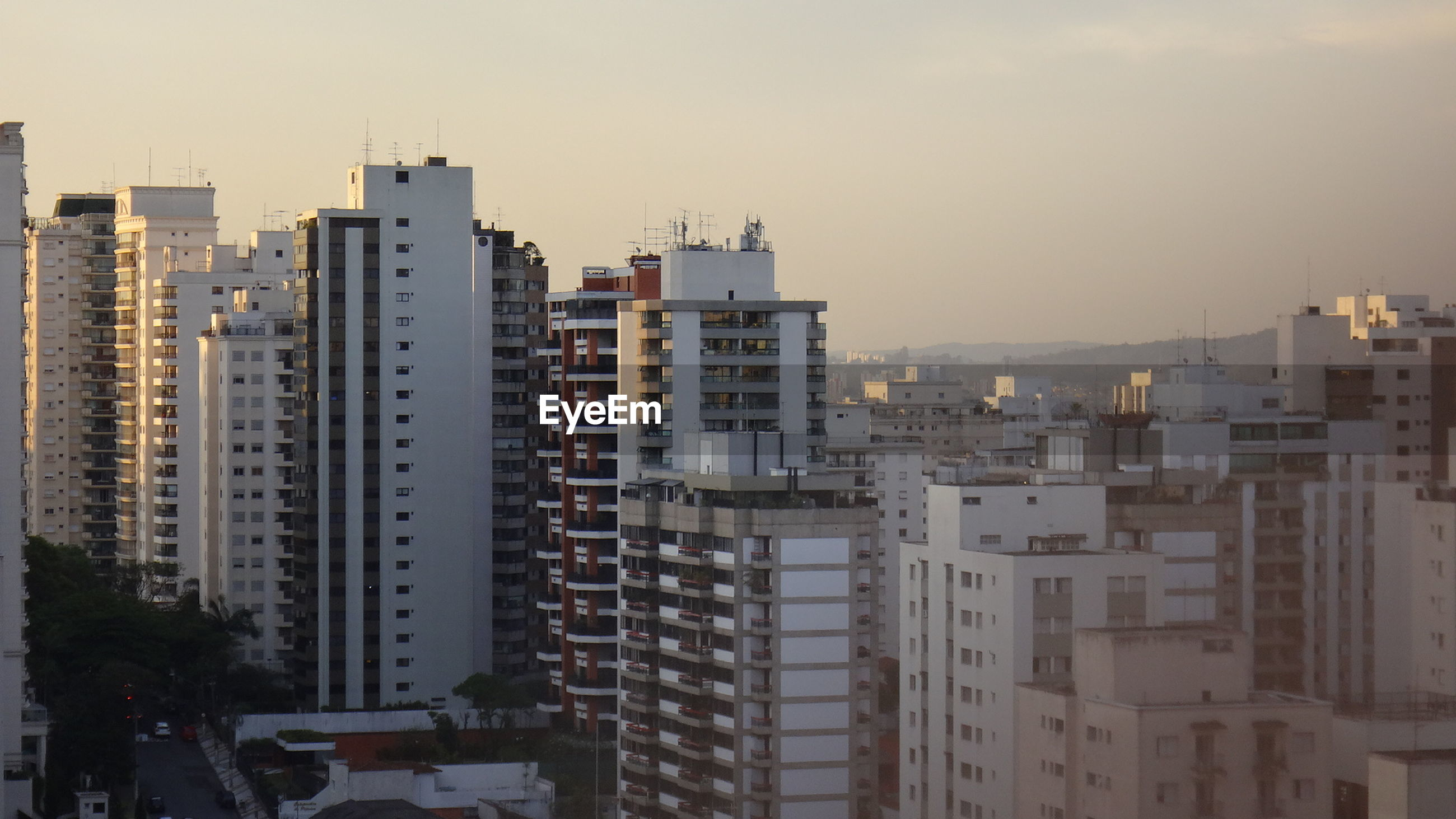 Residential buildings in city against sky during sunset
