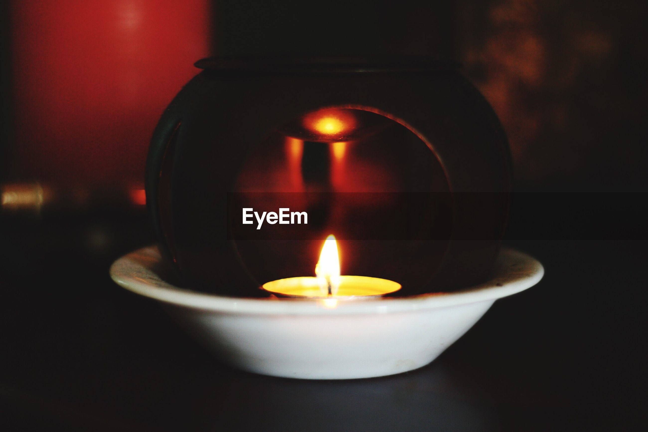 Close-up of lit tea light candle on table