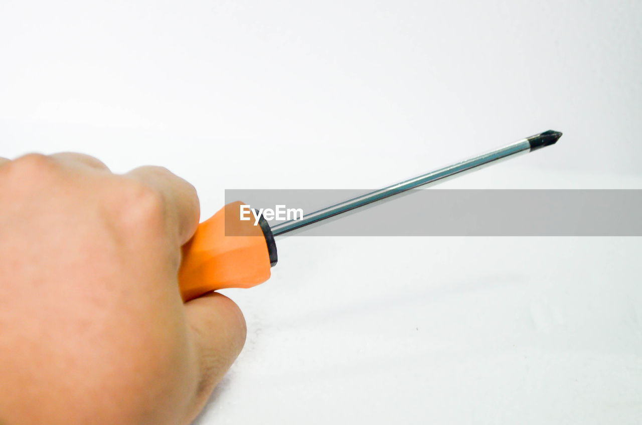 Close-up of man holding screwdriver over white background
