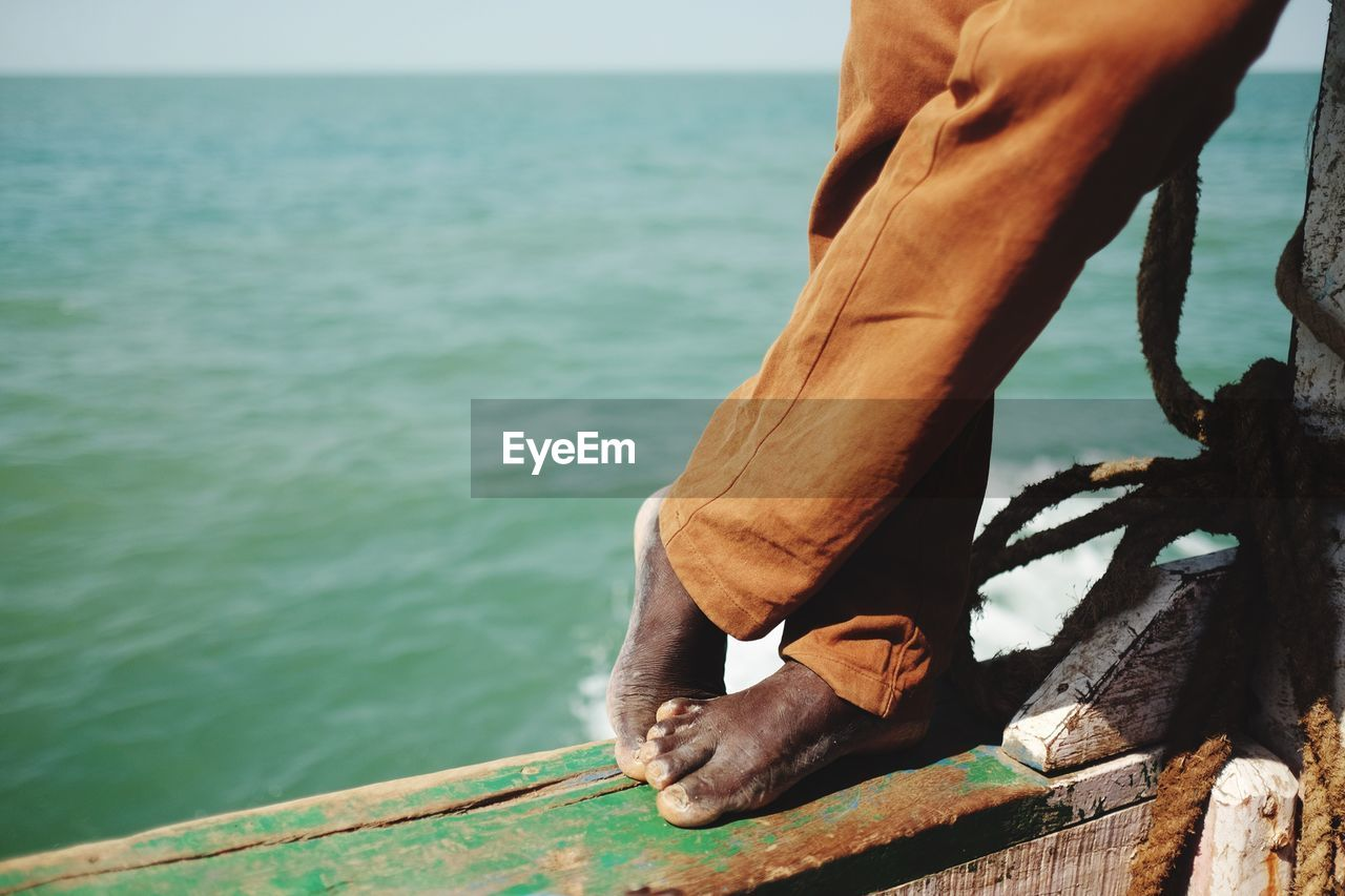 Low section of man standing on boat sailing in sea