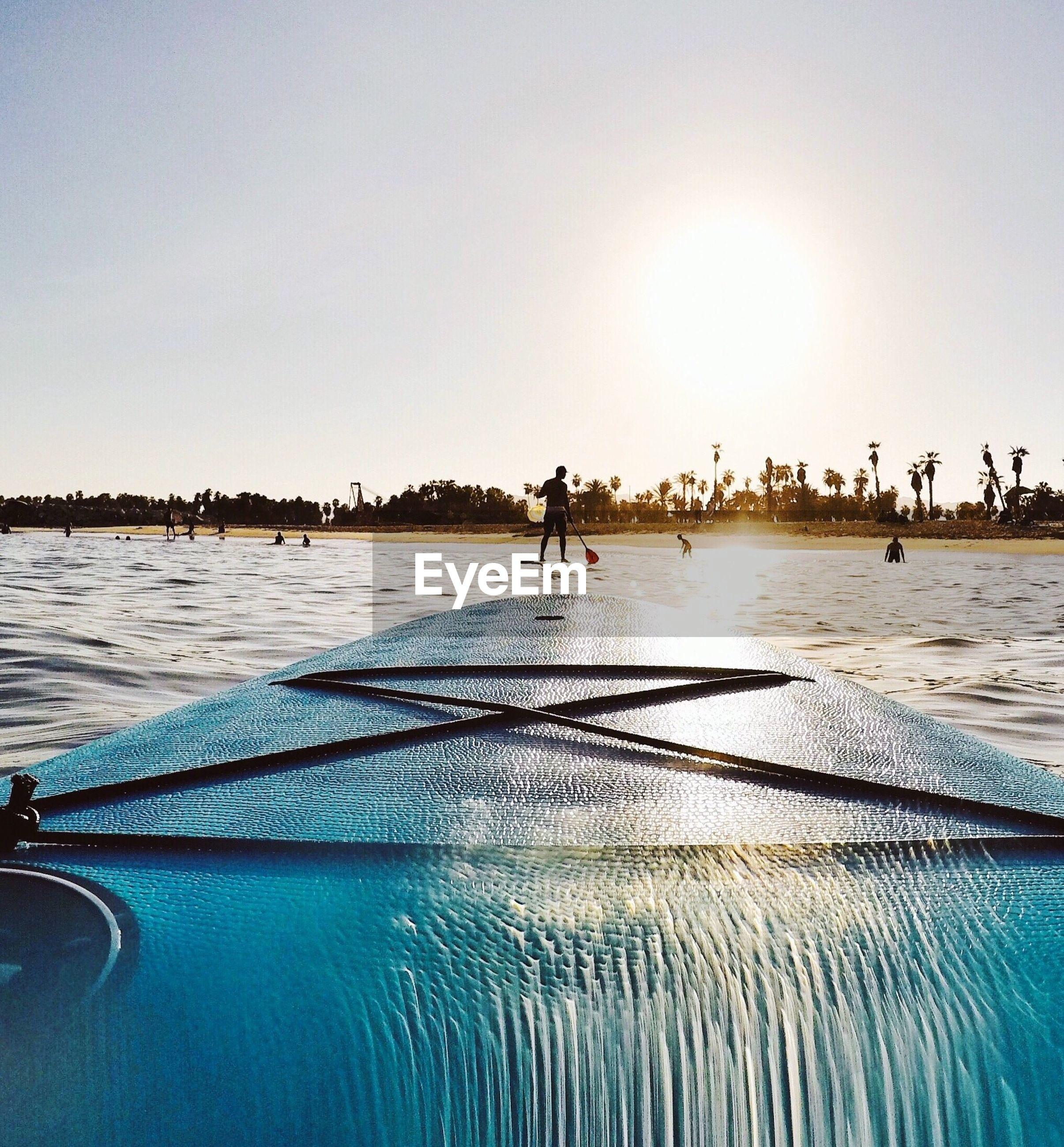 Surfboard on sea against sky at beach