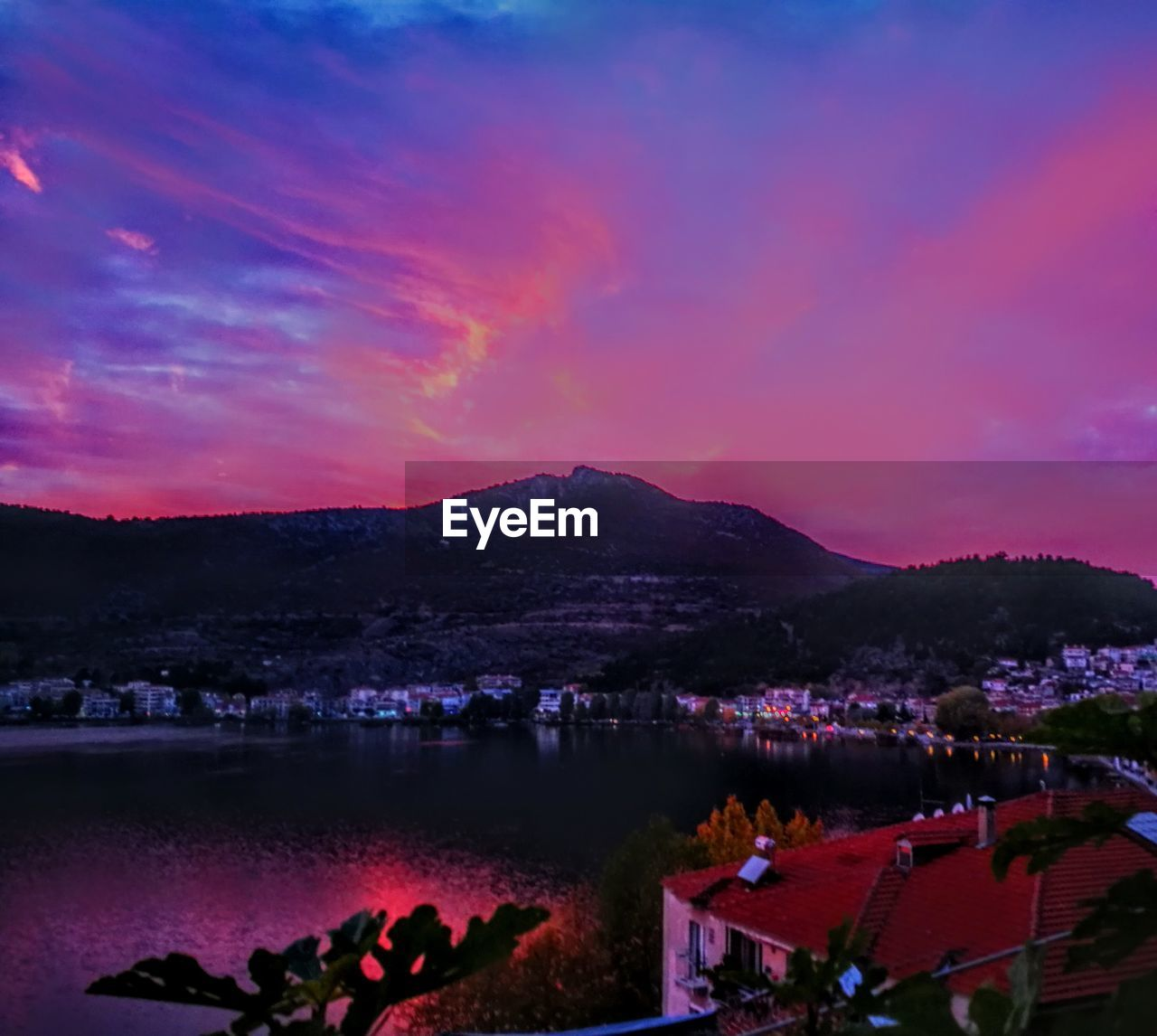 sunset, mountain, sky, building exterior, dusk, beauty in nature, scenics, lake, outdoors, nature, town, architecture, night, built structure, large group of people, water, illuminated, mountain range, tree, city, cityscape, people