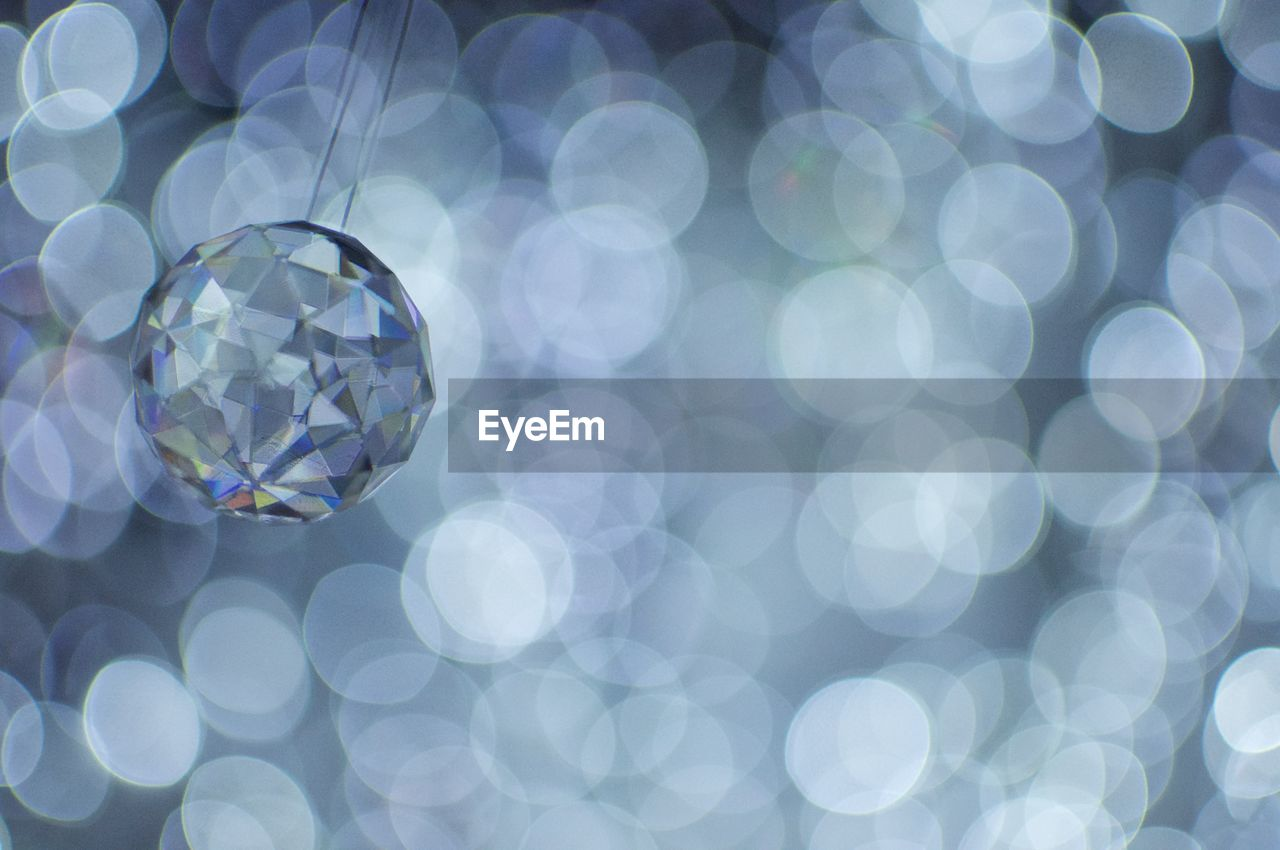sphere, close-up, no people, lens flare, shiny, shape, circle, geometric shape, transparent, pattern, reflection, blue, illuminated, focus on foreground, defocused, backgrounds, day, jewelry, design, crystal, outdoors, luxury, light