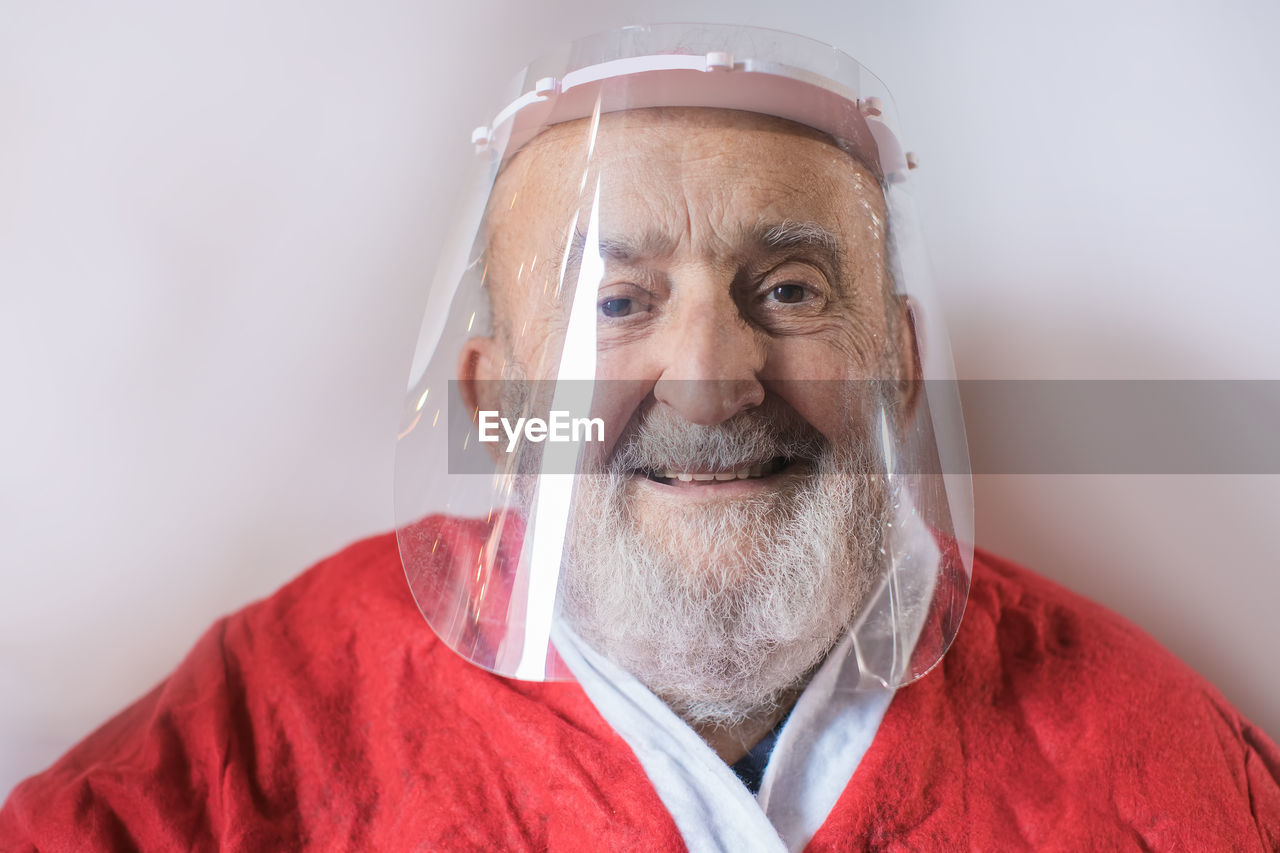 Close-up portrait of senior man wearing face shield against white background