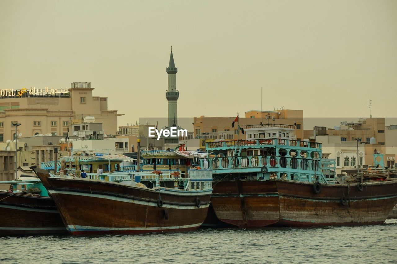 Boats Moored In Sea Against Buildings In City Against Clear Sky