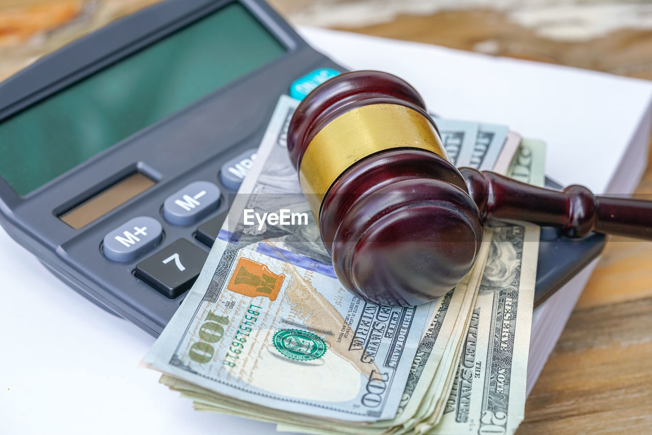 High angle view of paper currencies with gavel on wooden table