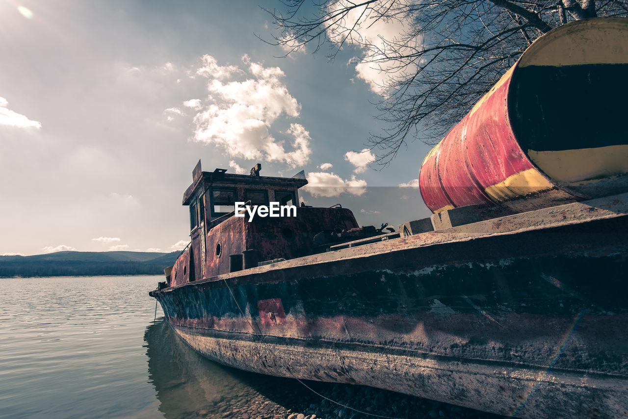Abandoned boat against sky