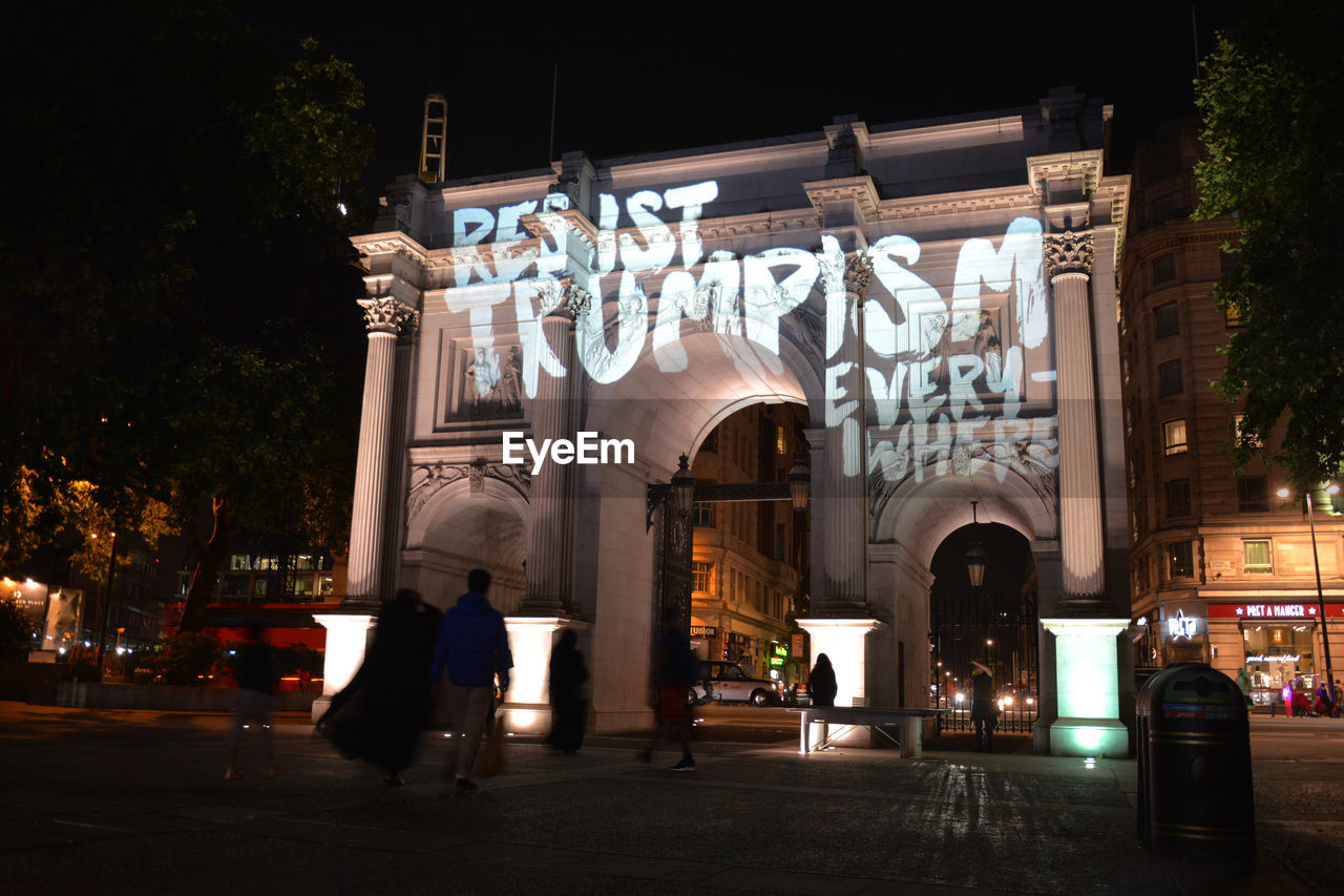 Low angle view of text on triumphal arch in city at night