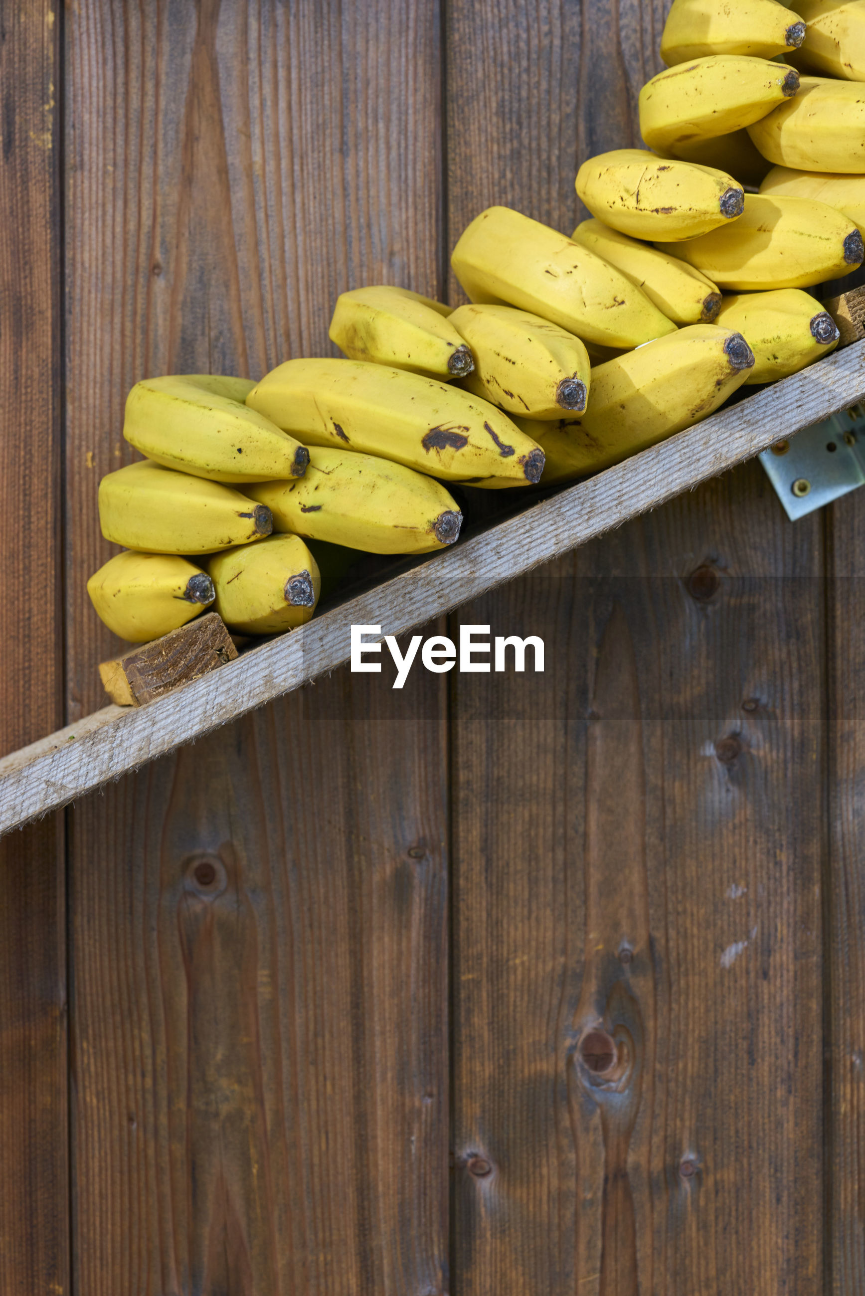 Bananas on shelf against wooden wall