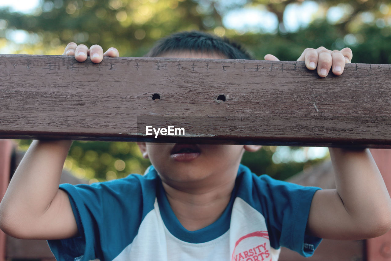 Close-Up Of Boy Playing With Wooden Railing