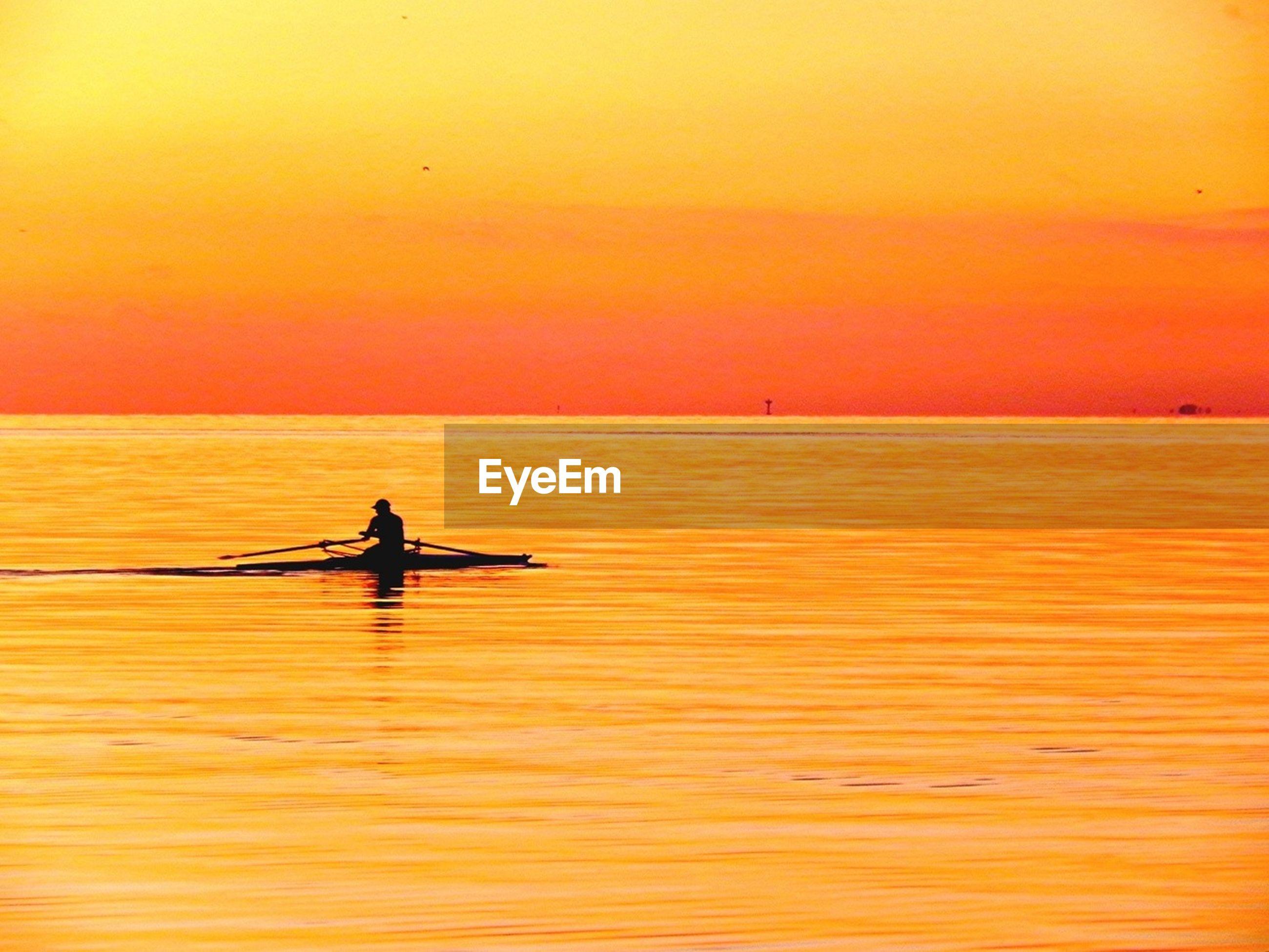 Silhouette man peddling boat in orange river