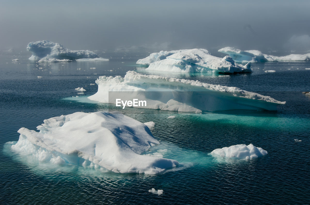Scenic View Of Icebergs In Sea Against Sky