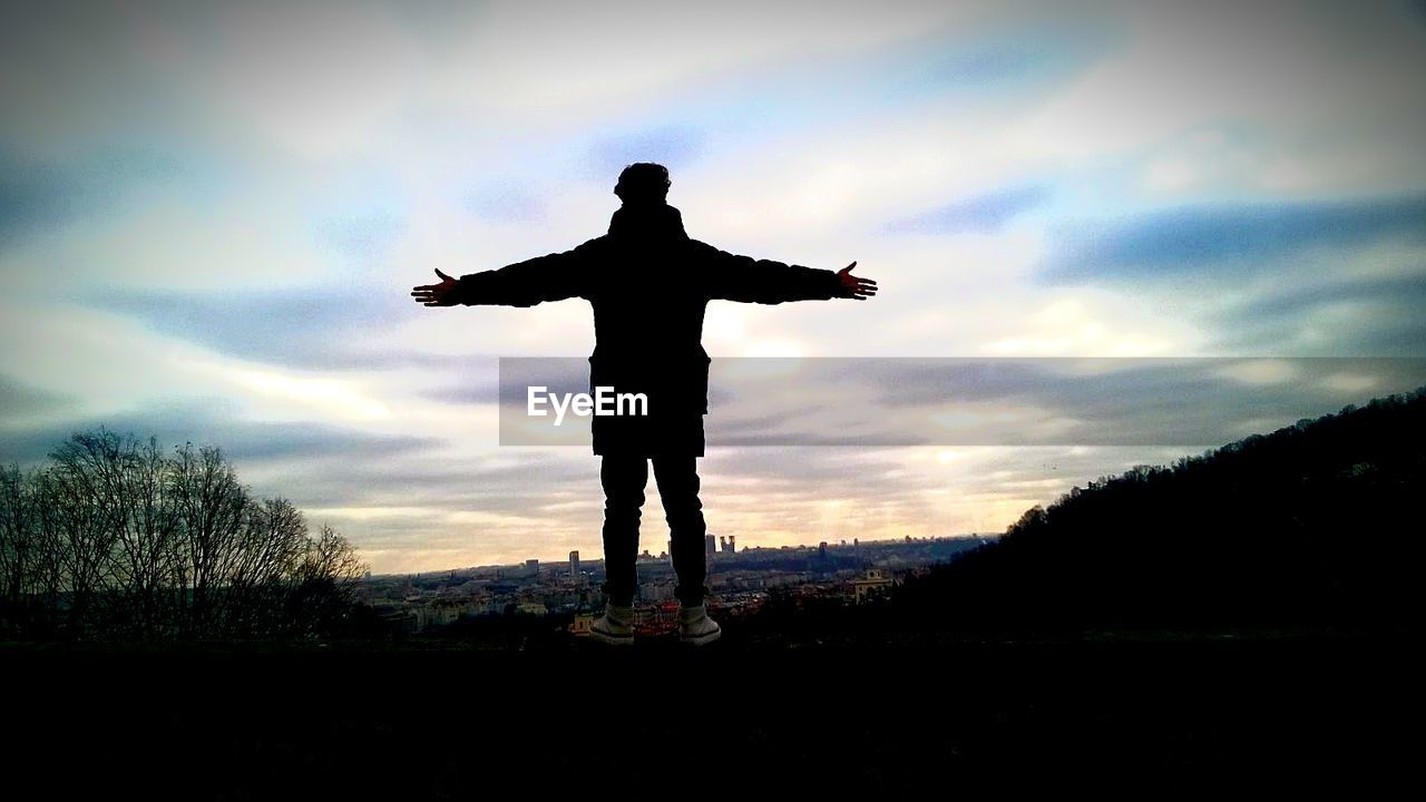 silhouette, sky, sunset, cloud - sky, full length, one person, arms outstretched, real people, men, outdoors, lifestyles, standing, nature, landscape, tree, scenics, childhood, day, energetic, people