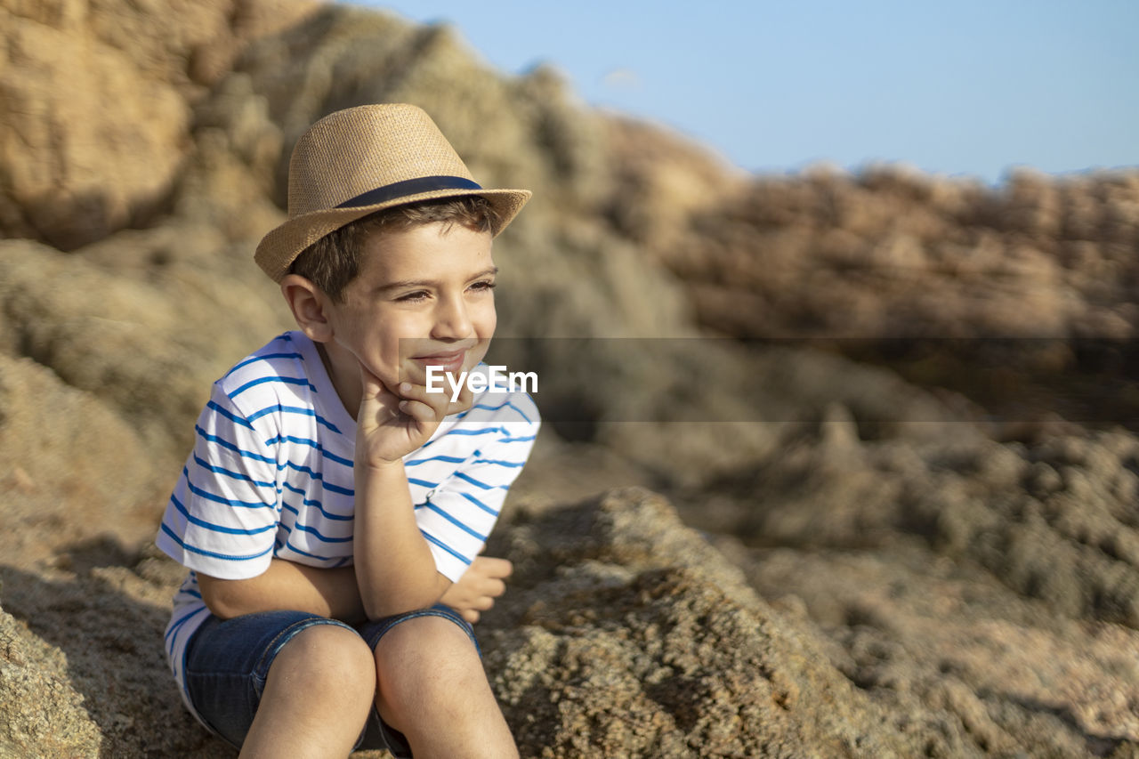 Cute boy wearing hat sitting on rock
