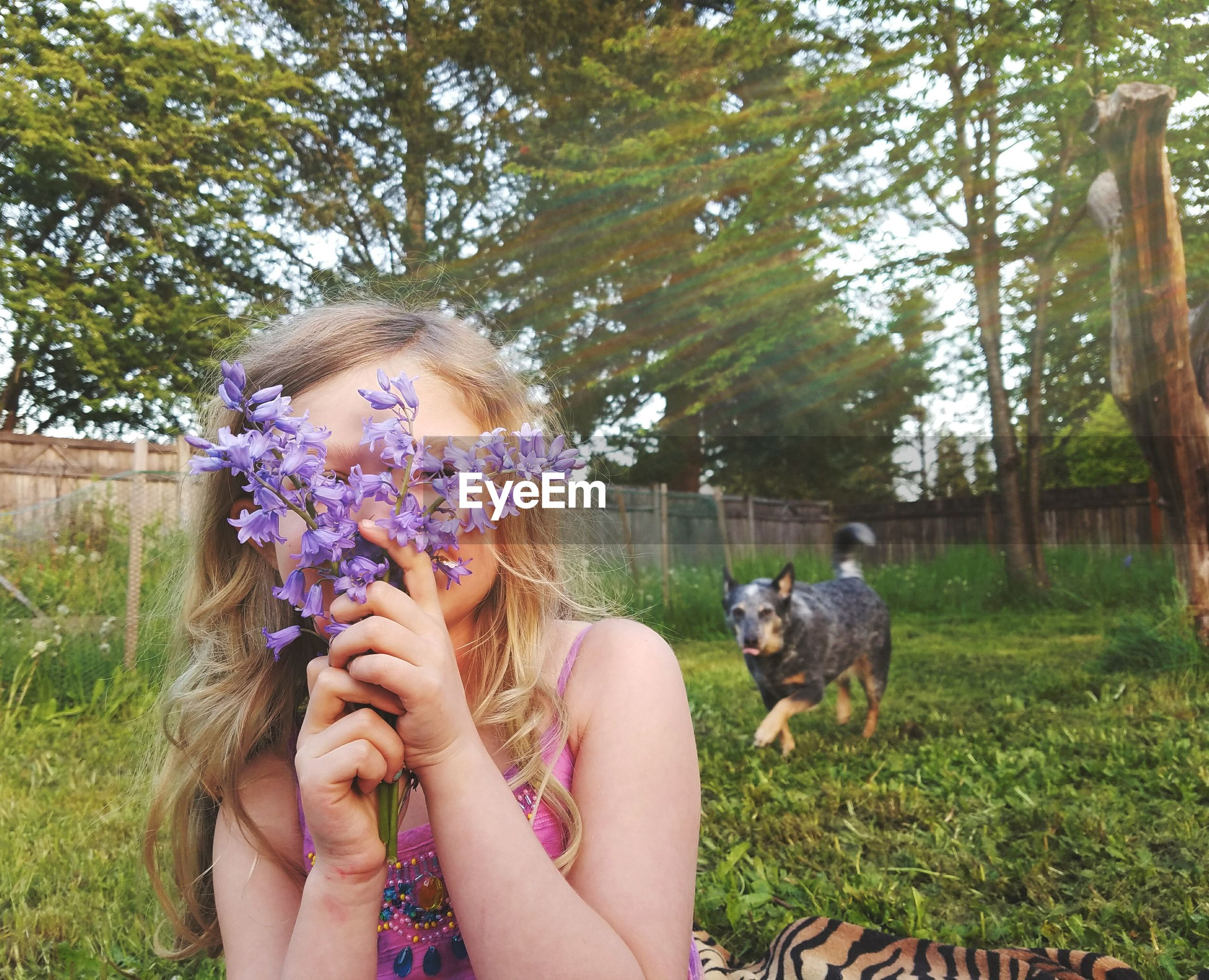 Girl hiding face with purple flowers in park