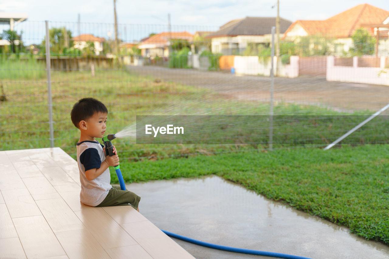 Cute boy water hose while sitting in yard