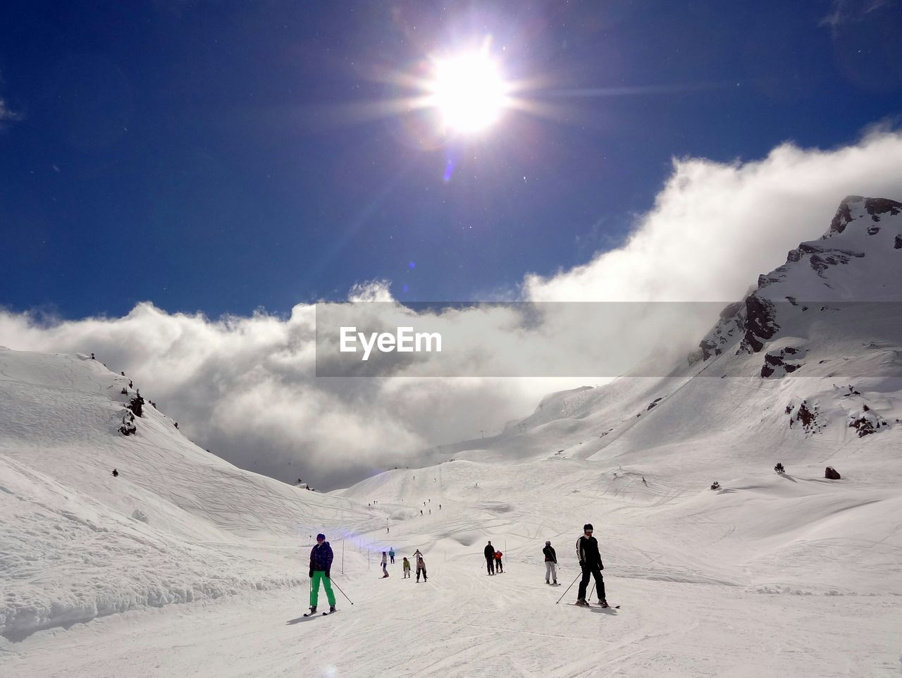 Low angle view of people skiing on snowcapped mountains on sunny day
