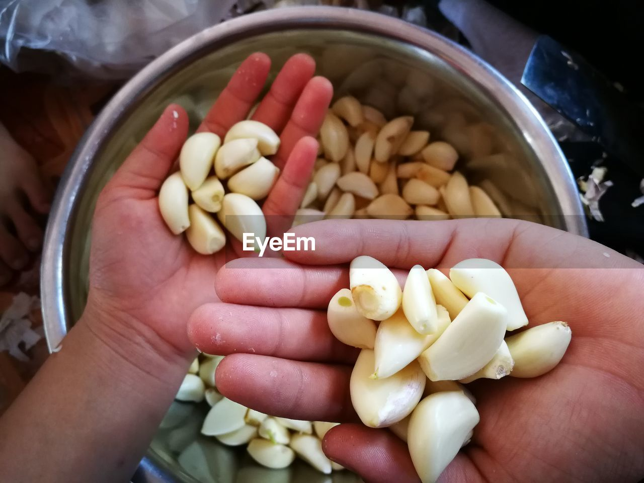 Cropped Hands Of People Holding Garlic