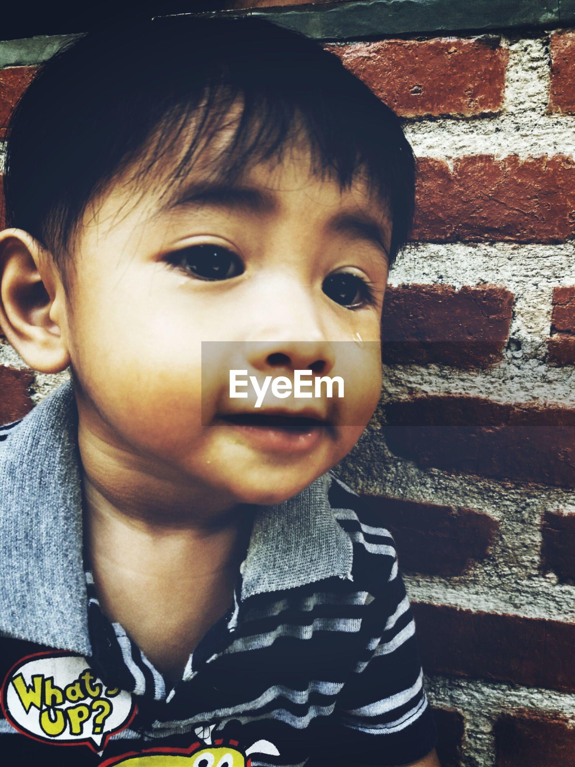 Close-up cute boy against wall