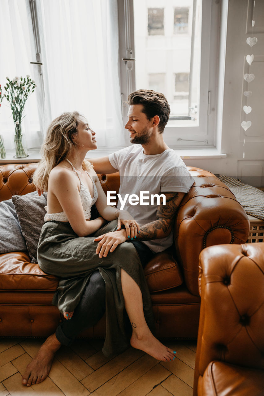 sitting, two people, young adult, indoors, young men, young women, full length, real people, togetherness, couple - relationship, sofa, home interior, lifestyles, furniture, women, heterosexual couple, casual clothing, men, young couple, beautiful woman, positive emotion