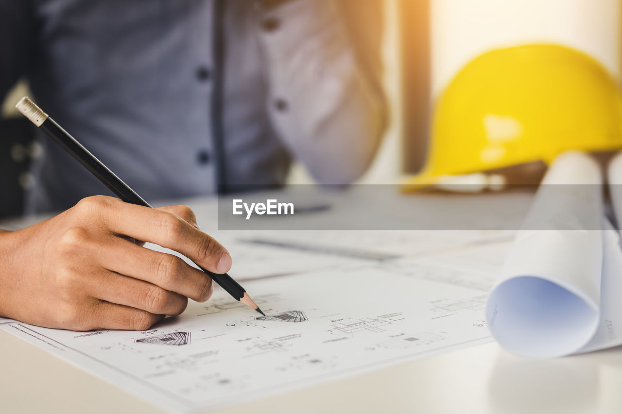 Midsection of engineer with pencil analyzing blueprint on table