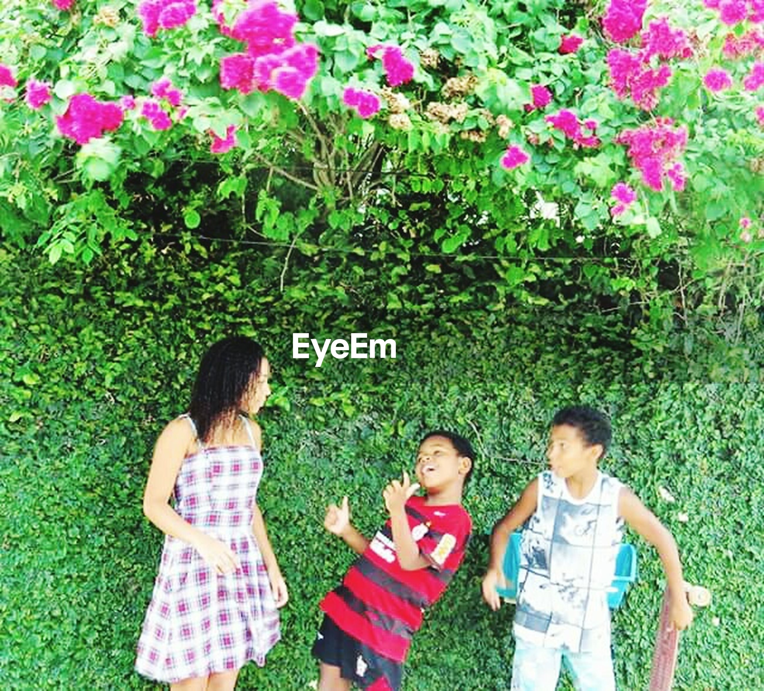 lifestyles, childhood, leisure activity, togetherness, bonding, girls, elementary age, love, casual clothing, boys, grass, family, innocence, park - man made space, person, sitting, growth, flower