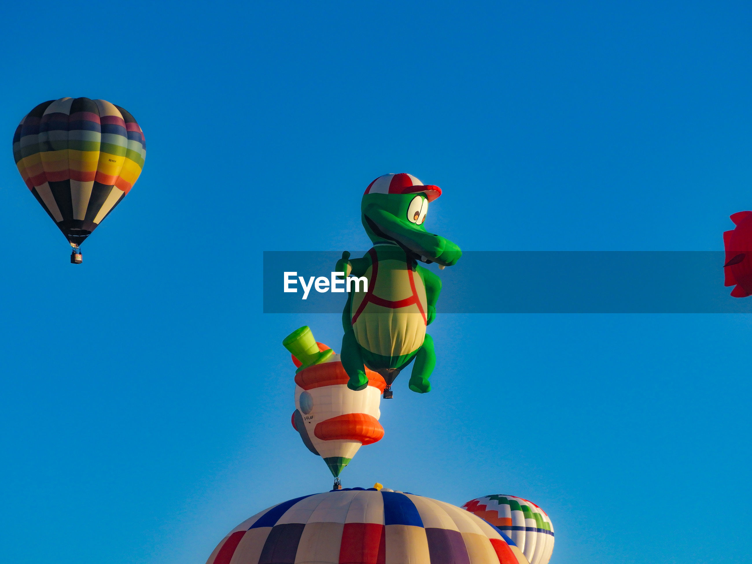 Low angle view of balloons against clear blue sky