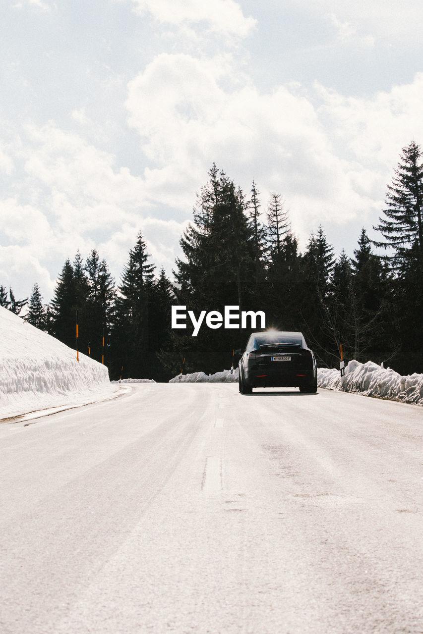 CAR ON SNOW AGAINST TREES