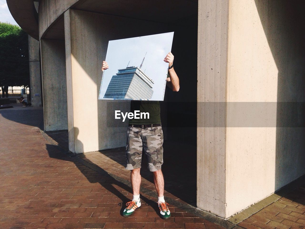 Man holding photograph of building while standing on sidewalk