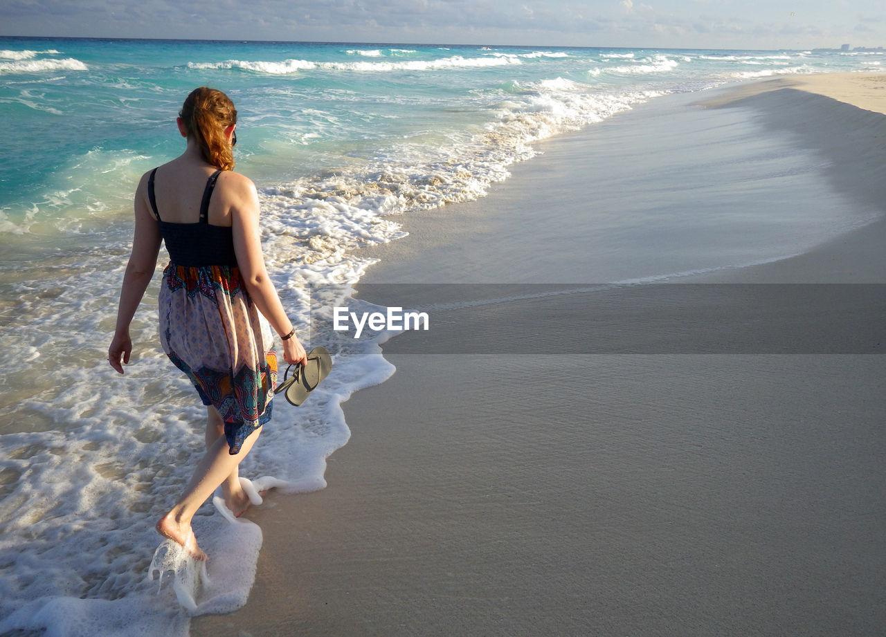 Woman Walking On Shore At Beach