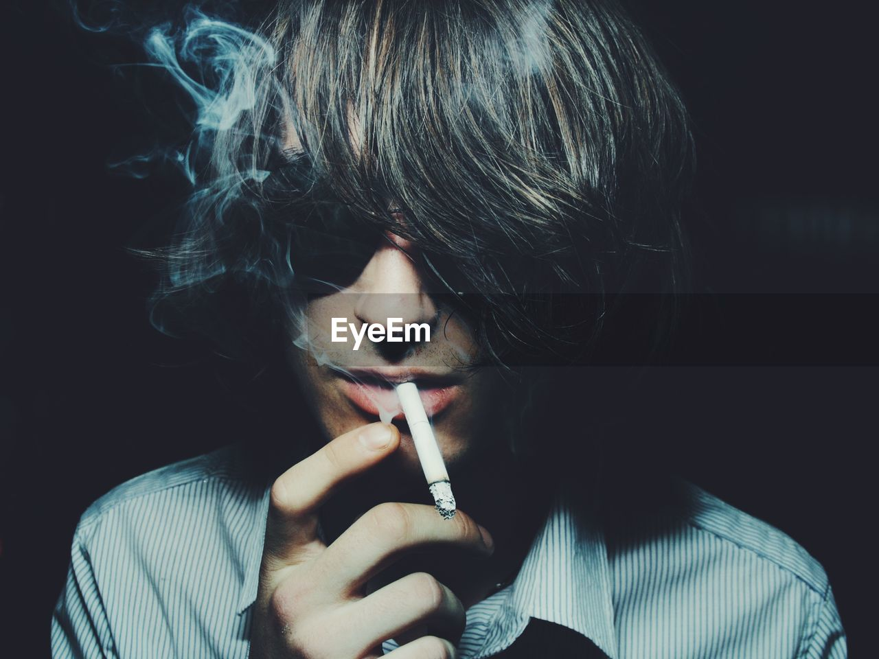 Portrait of young man holding cigarette