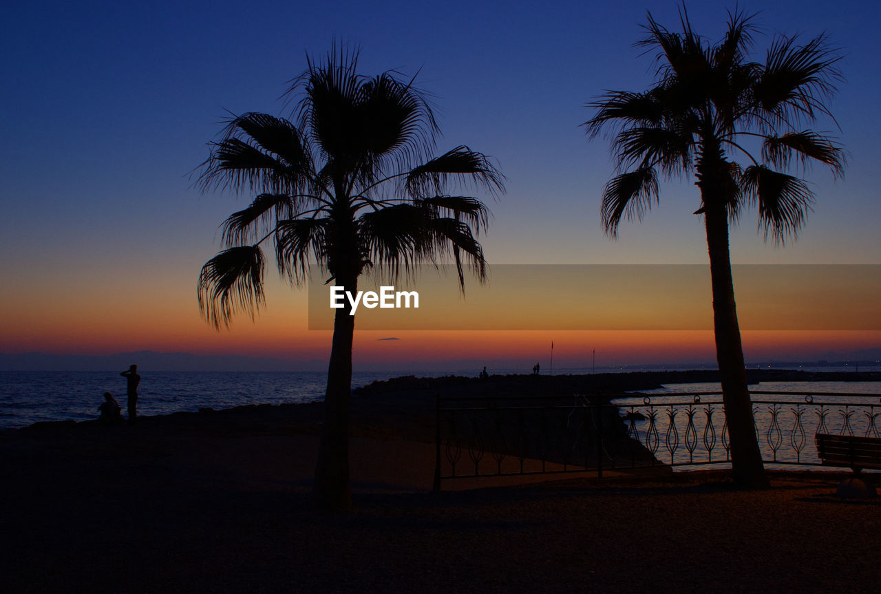 Silhouette palm trees on beach against clear sky at sunset