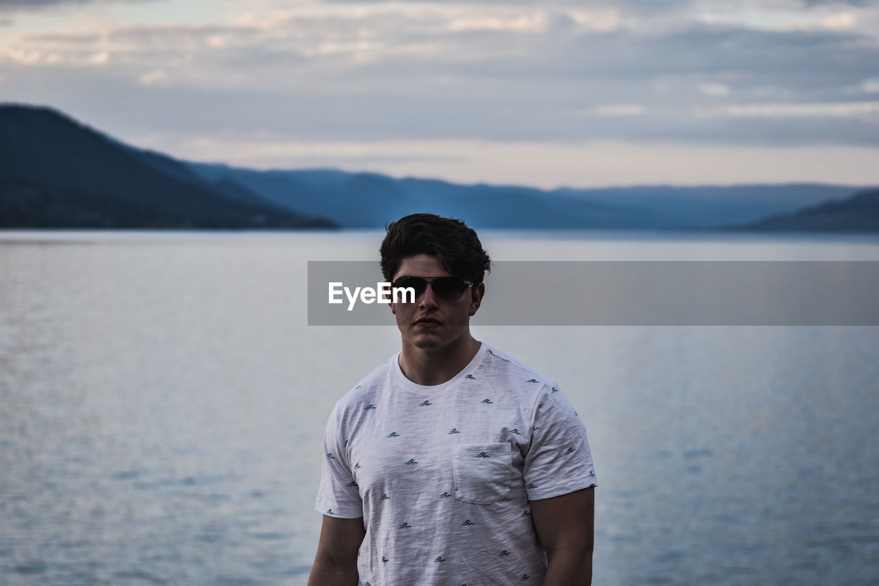 Portrait Of Confident Young Man Wearing Sunglasses Against Lake During Sunset