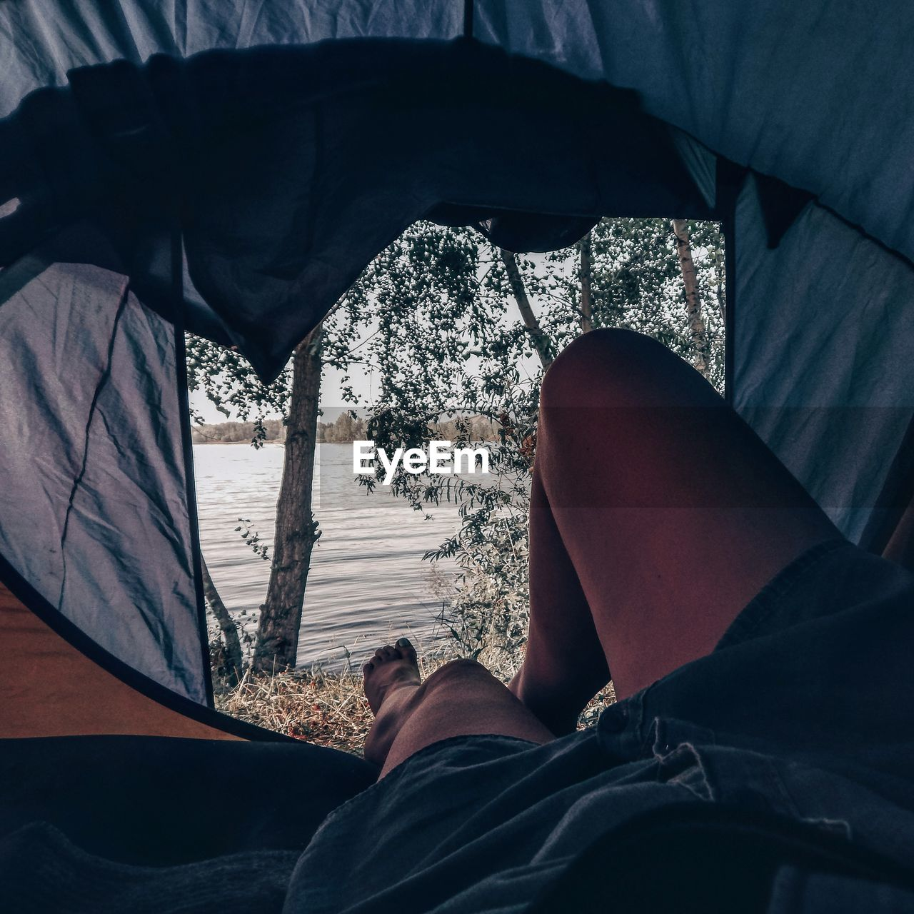 Low section of man relaxing by lake in tent