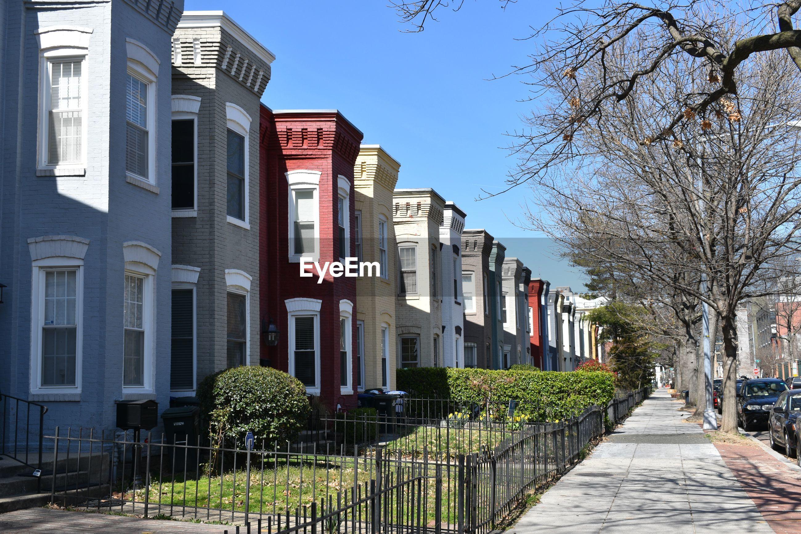 FOOTPATH AMIDST BUILDINGS AGAINST CLEAR SKY