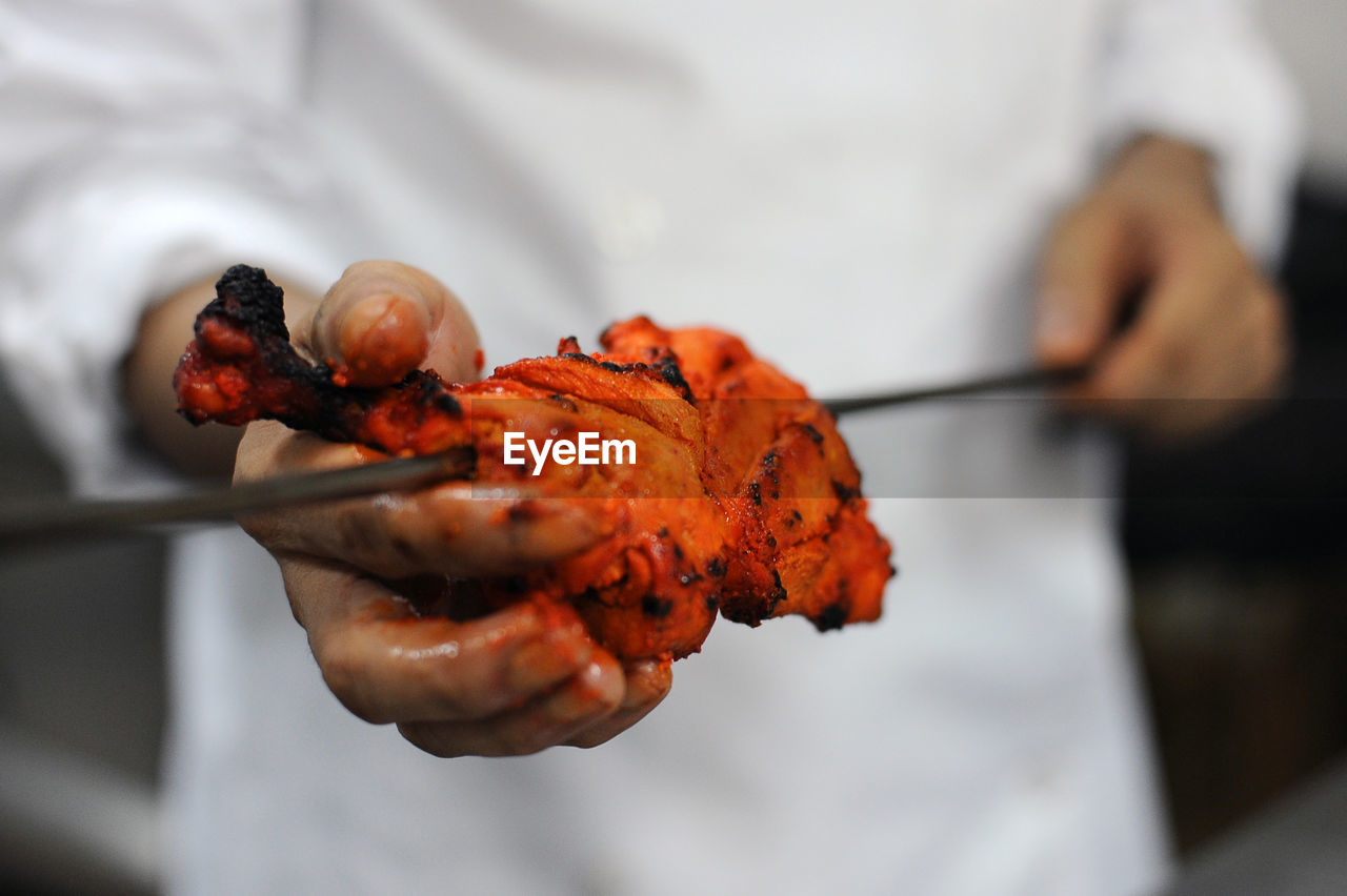 Cook Preparing Chicken In Curry And Spices