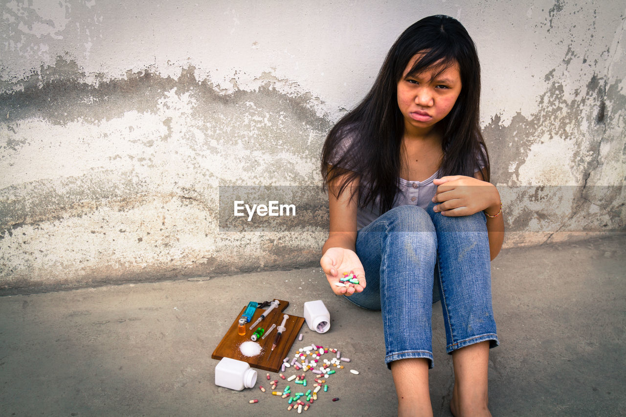 Depressed Teenage Girl Sitting By Narcotics Against Wall