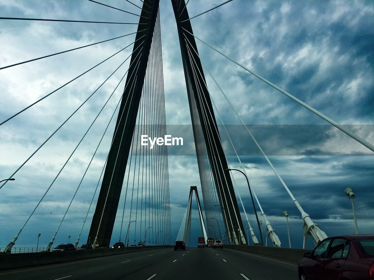 connection, suspension bridge, bridge - man made structure, engineering, transportation, sky, architecture, built structure, cloud - sky, car, road, outdoors, land vehicle, cable, day, the way forward, travel, bridge, mode of transport, travel destinations, city, low angle view, no people