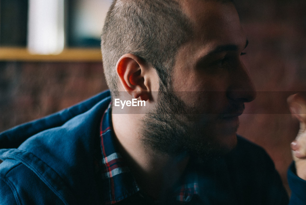 Close-Up Of Young Bearded Man Sitting In Restaurant