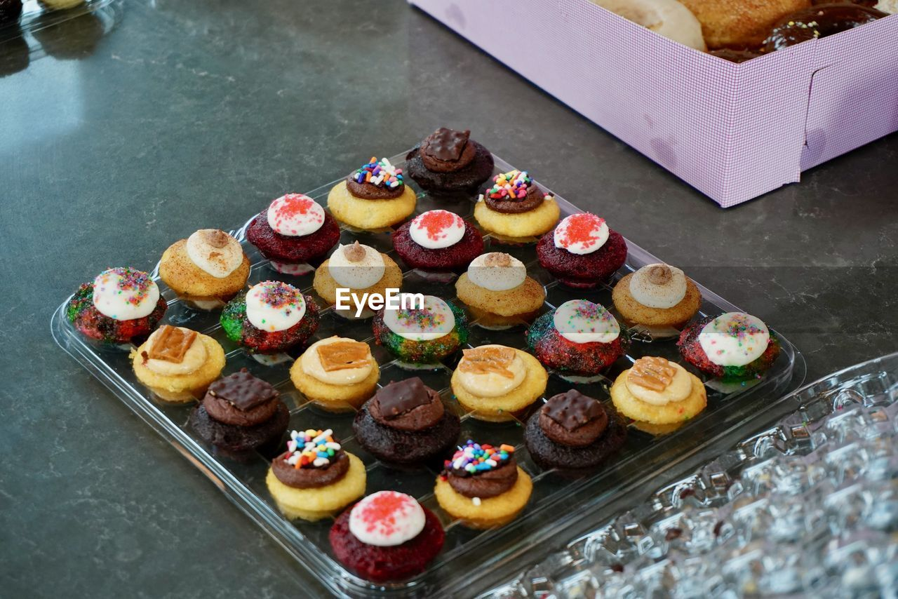 food and drink, food, sweet food, indulgence, sweet, freshness, dessert, ready-to-eat, unhealthy eating, high angle view, baked, retail, temptation, cake, arrangement, in a row, no people, still life, large group of objects, retail display, tray, order, snack, display cabinet