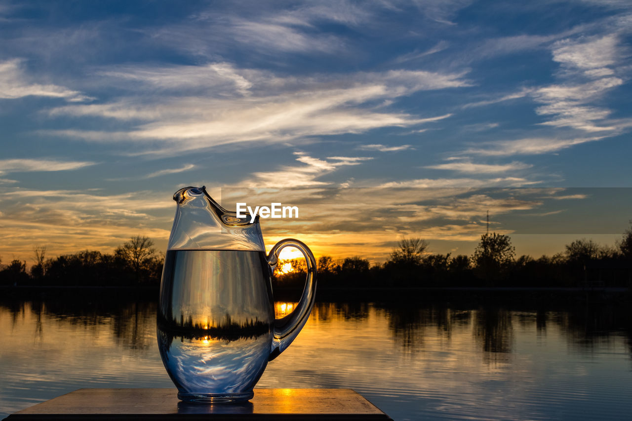 Lake Seen Through Jug At Table Against Sky During Sunset