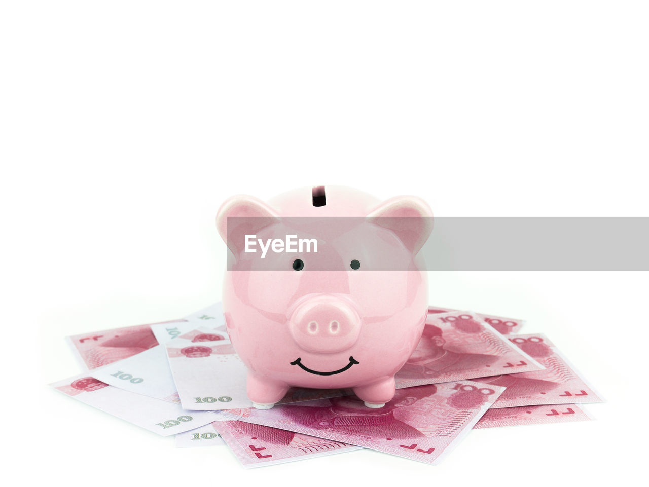 Close-up of piggy bank with paper currencies against white background