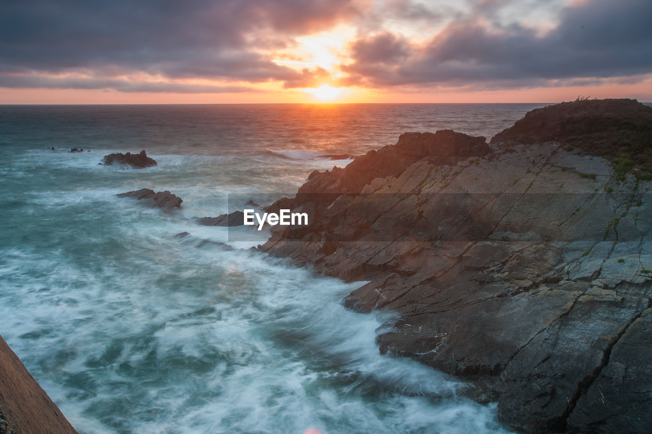 sky, sunset, scenics - nature, cloud - sky, beauty in nature, water, sea, idyllic, beach, land, nature, motion, tranquil scene, rock, horizon, tranquility, horizon over water, non-urban scene, no people, outdoors, power in nature