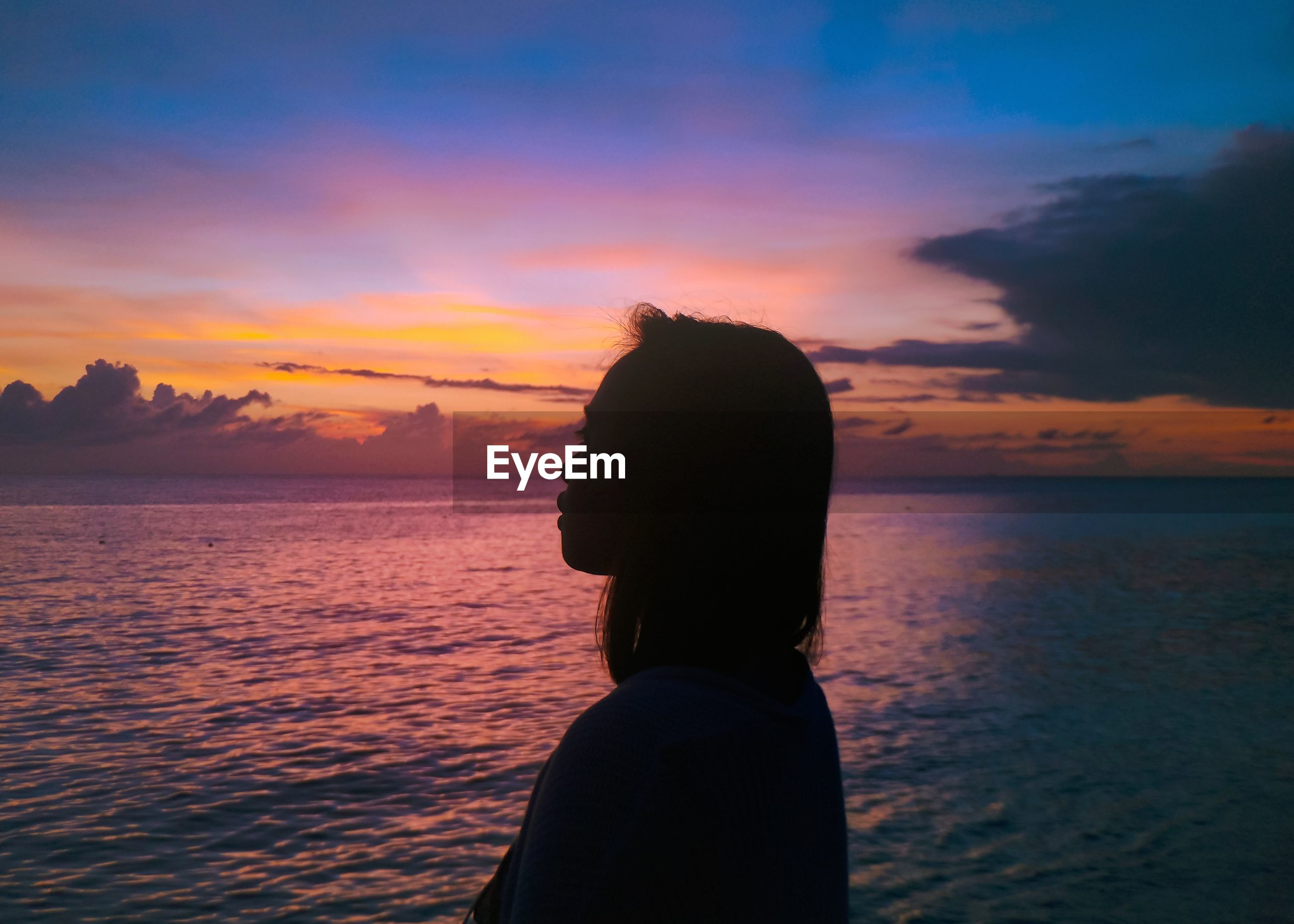 View of woman looking at sea against sky during sunset